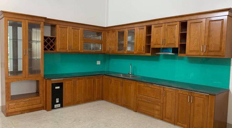 Tủ bếp gỗ sồi Nga dáng chữ L với kính bếp màu xanh cổ vịt hiện đại
