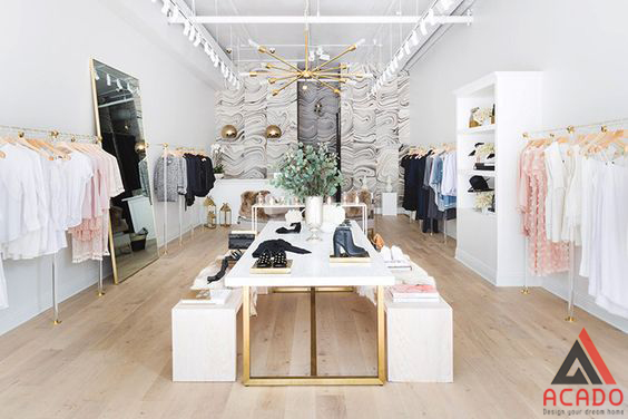 Shop quần áo tone chủ đạo màu trắng kết hợp với một chút gỗ làm điểm nhấn.