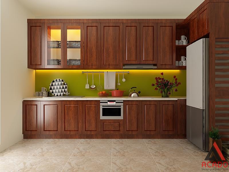 Tủ bếp xoan đào chữ i sơn màu cánh gián đậm kết hợp với kính bếp xanh.