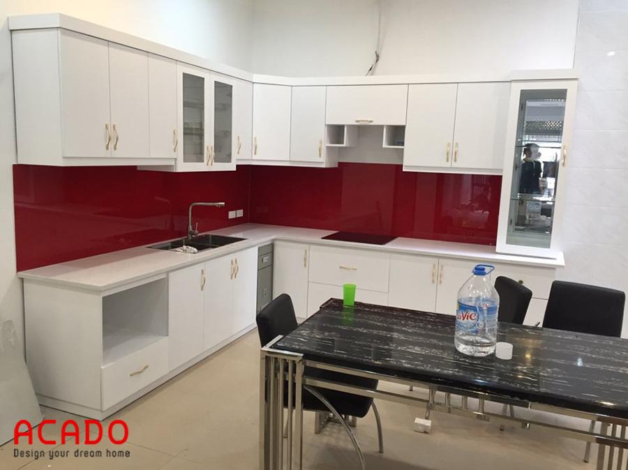 Tủ bếp màu trắng với điểm nhấn kính ốp bàn bếp màu đỏ.