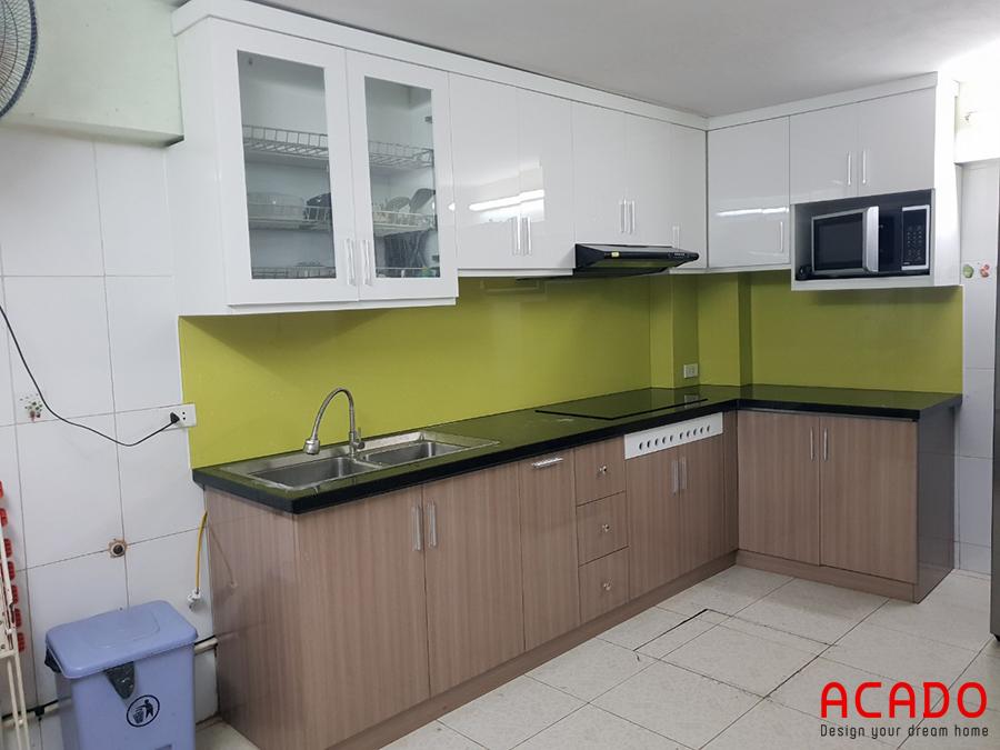 Tủ bếp Acrylic chữ L với điểm nhấn kính ốp bàn bếp màu xanh non.