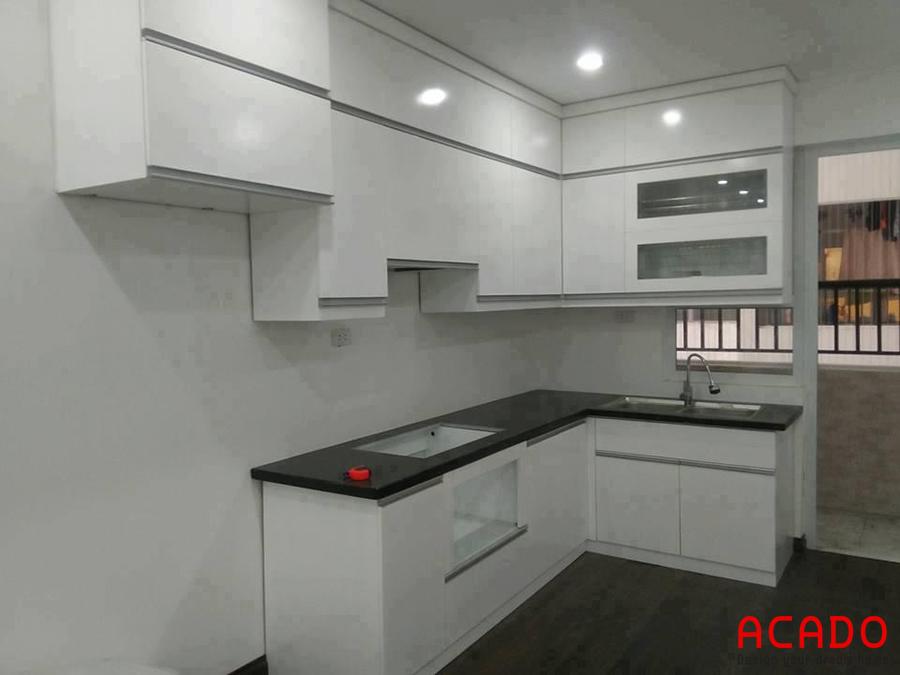 Tủ bếp chữ L màu trắng mở rộng không gian bếp.
