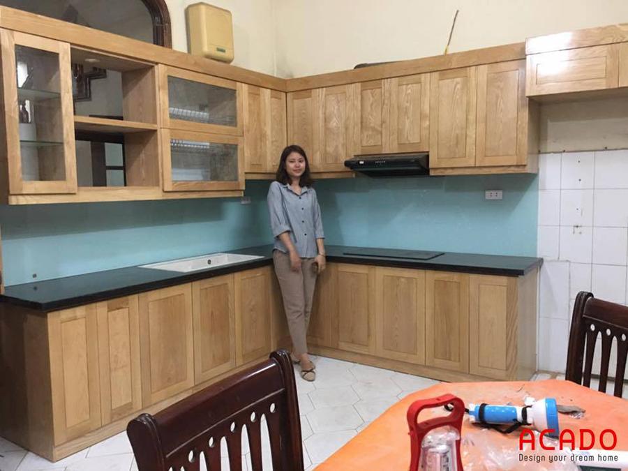 Bộ tủ bếp gỗ sồi tự nhiên phủ sơn bóng giữ lại đường vân gỗ và màu sắc vốn có của gỗ kết hợp với kính ốp tường màu xanh nhạt tạo cảm giác hài hòa, ấm cúng cho căn bếp