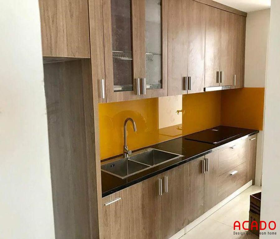 Mãu tủ bếp Melamine màu vân gỗ kết hợp kính màu cam đem lại sự sang trọng và hiện đại