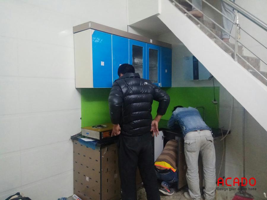 Hình ảnh đội ngũ thi công của Acado đang lắp tủ bếp inox 304 chữ L kết hợp cánh tủ Acrylic an cường cho gia chủ