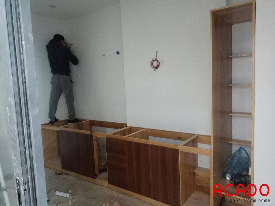 Thợ của Acado đang thi công lắp tủ dưới với chất liệu là gỗ sồi