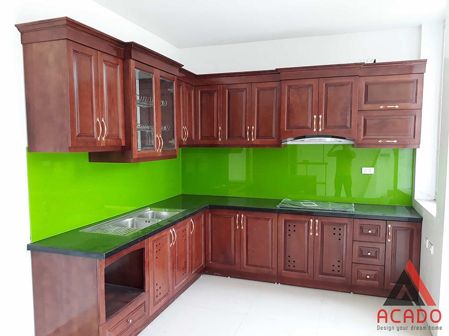 Mẫu tủ bếp gỗ xoan đào hình chữ L màu cánh dán đậm với điểm nhấn là kính ốp màu xanh