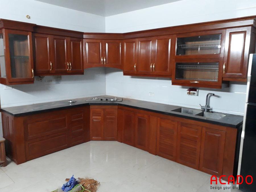 Mẫu tủ bếp gỗ xoan đào hình chữ L màu cánh dán đậm tận dụng không gian góc của phòng bếp