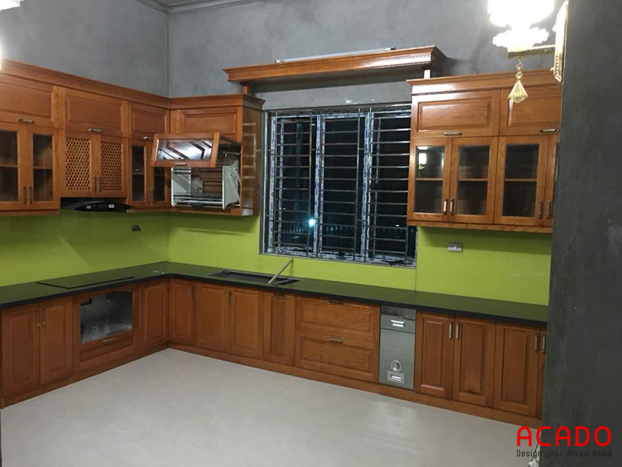 Mẫu tủ bếp gỗ xoan đào màu cánh dán đậm được thiết kế thông minh vẫn tận dụng được của sổ