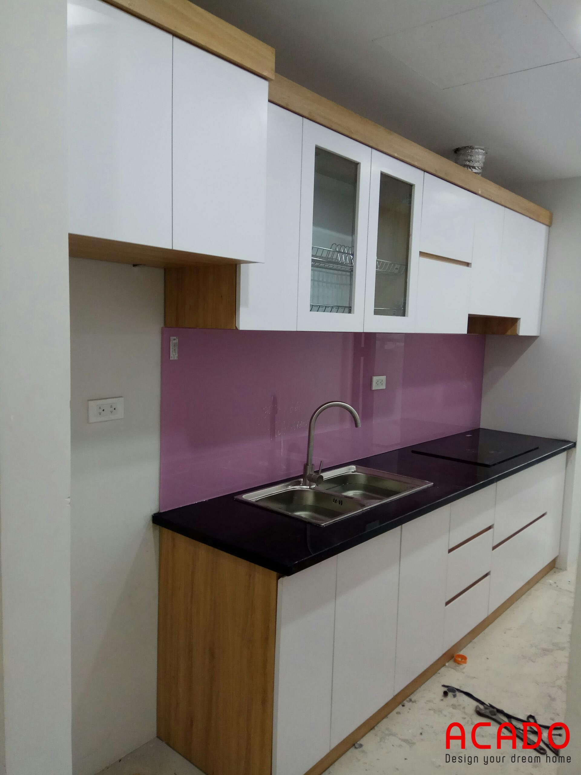 Mẫu tủ bếp Melamine màu trắng với điểm nhấn là kính ốp màu tím cá tính, hiện đại