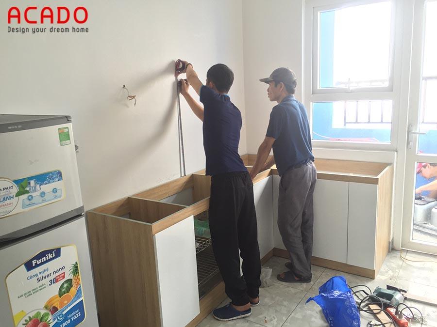 Thợ của Acado đang đo đạc để lắp tủ trên