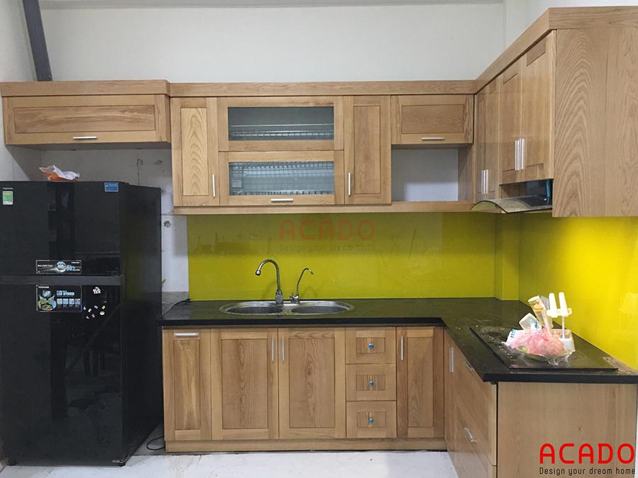 Mẫu tủ bếp gỗ sồi Nga hình chữ L với điểm nhấn là kính ốp màu vàng