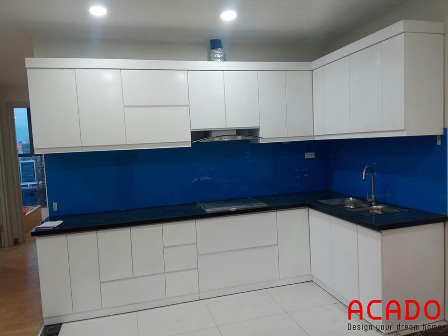 Tủ bếp Melamine hình chữ L màu trắng với điểm nhấn là kính ốp màu xanh cho không gian bếp thoải mái và tiện nghi