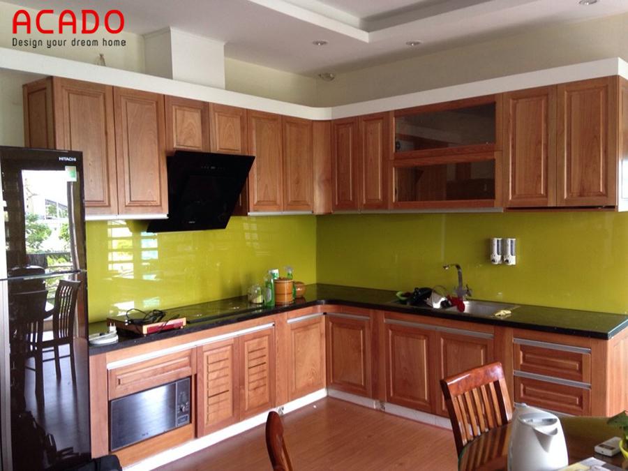 Mẫu tủ bếp gỗ sồi Mỹ hình chữ L kết hợp kính ốp màu vằng tạo cảm giác ấm cúng
