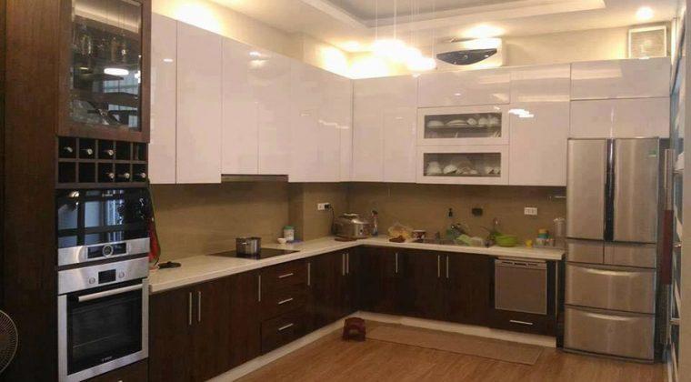 Mẫu tủ bếp đẹp bằng chất liệu gỗ công nghiệp acrylic bóng gương. Thiết kế theo dáng chữ L bố trí đầy đủ công năng sử dụng
