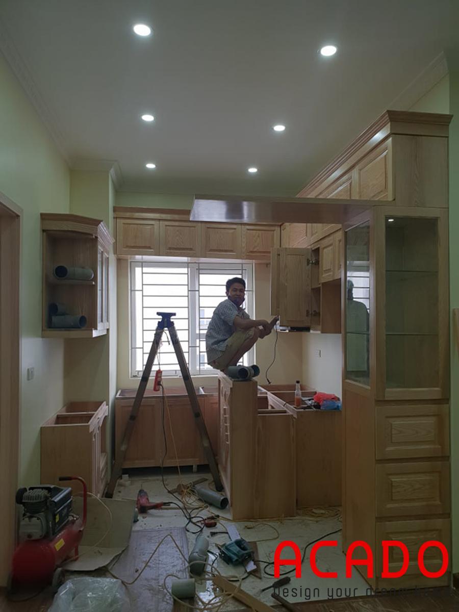 CHú thợ đang vui vẻ lắp đặt tủ trên.