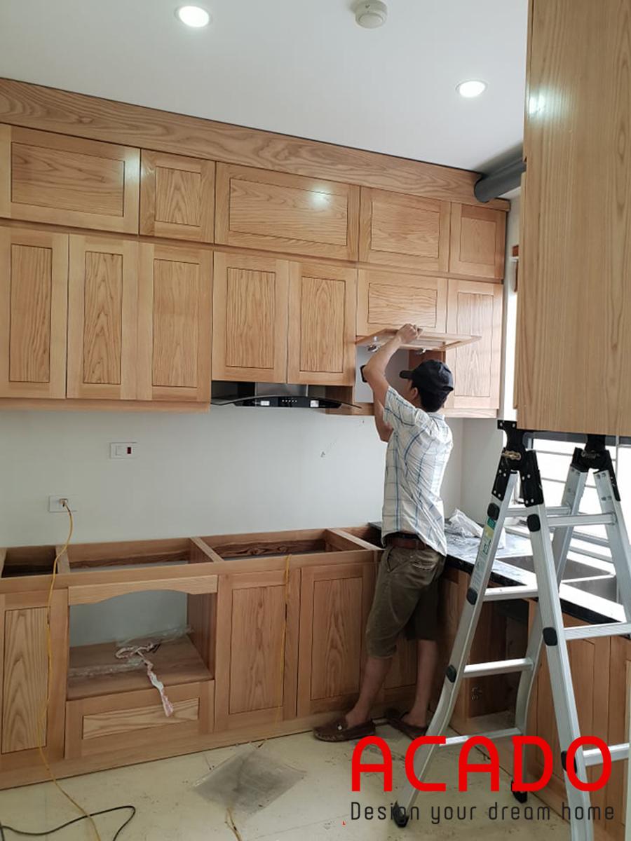Thợ đang hoàn thiện tủ bếp trên.