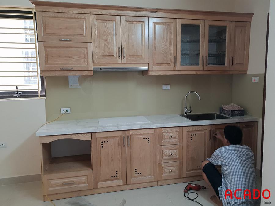 Thợ điện nước thực hiện những bước cuối cùng để hoàn thiện tủ bếp.