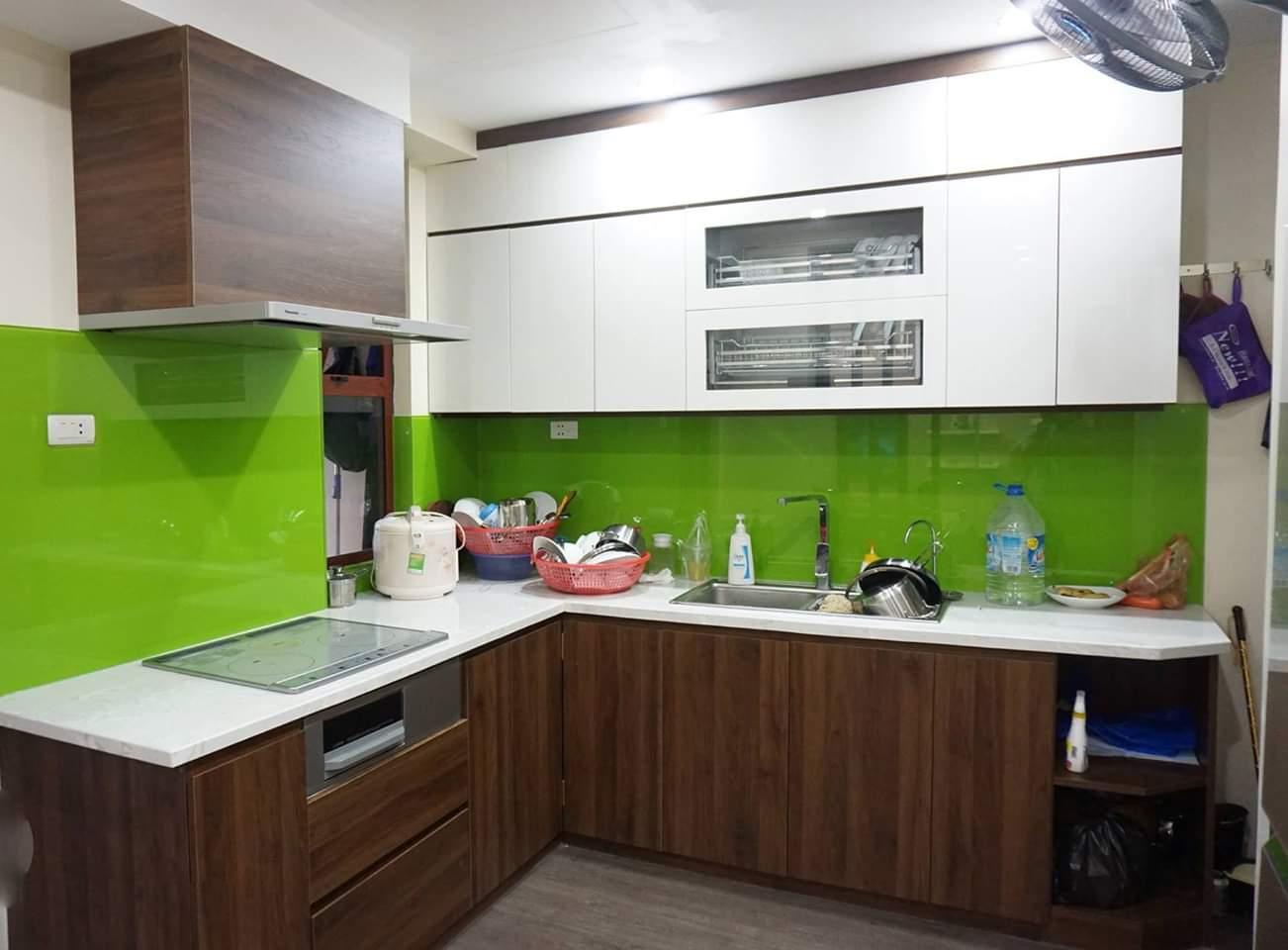 Tủ bếp dáng chữ L với điểm nhấn là kính ốp bàn bếp màu xanh non.