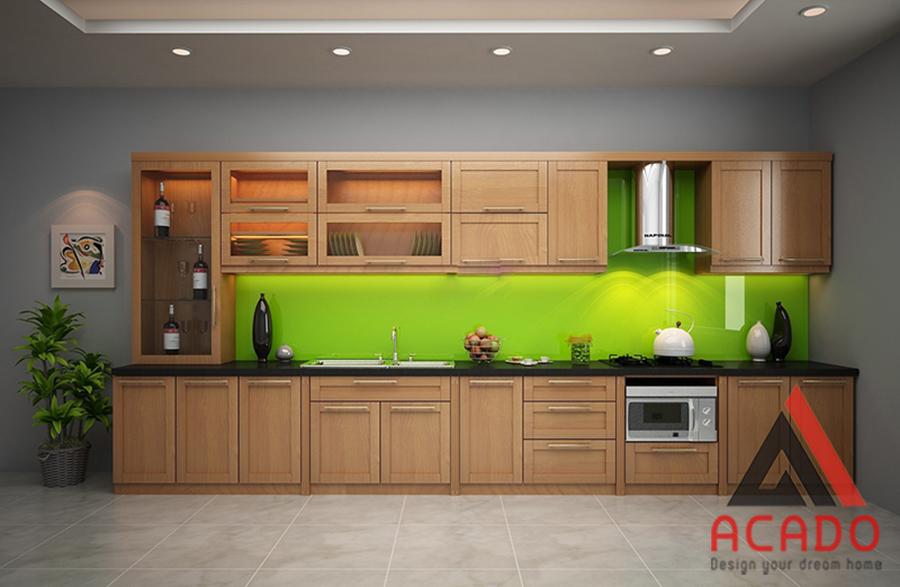 Tủ bếp gỗ sồi Mỹ với điểm nhấn là kính ốp bàn bếp màu xanh non.