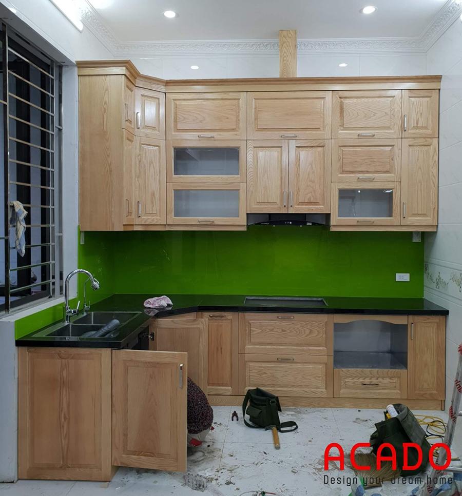 Mẫu tủ bếp kết hợp kính ốp bàn bếp màu xanh.