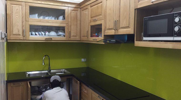 Tủ bếp lắp thêm kính ốp bàn bếp màu xanh thêm phần hiện đại, sang trọng.