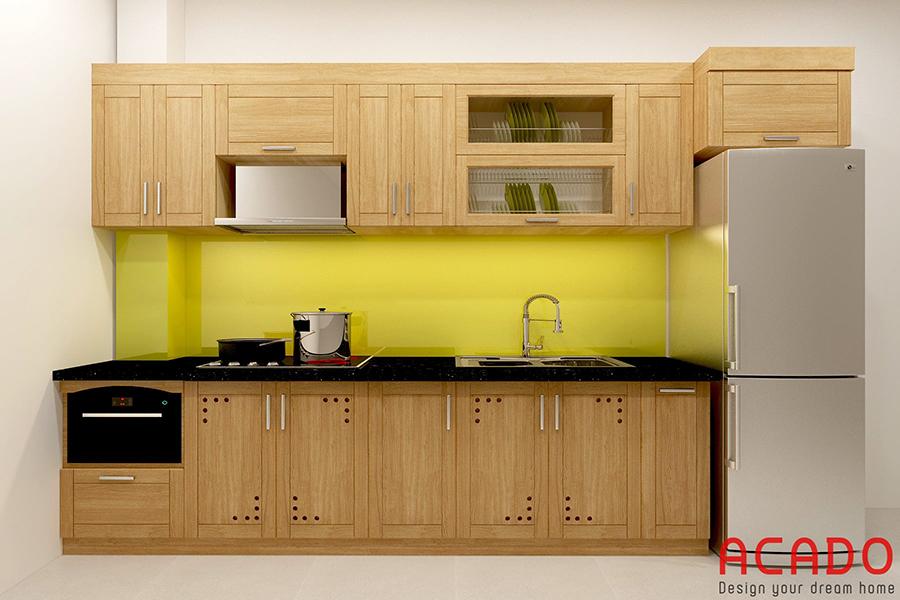 Một mẫu tủ bếp gỗ sồi dáng chữ I khác với kính ốp bàn bếp màu vàng.