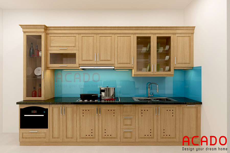 Tủ bếp gỗ sồi Mỹ với điểm nhấn kính ốp bàn bếp màu xanh.