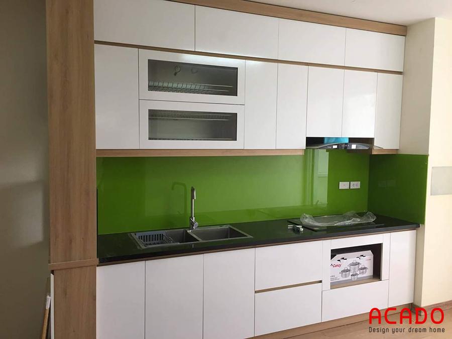 Tủ bếp tông màu trắng với điểm nhấn kính ốp bàn kính màu xanh non.