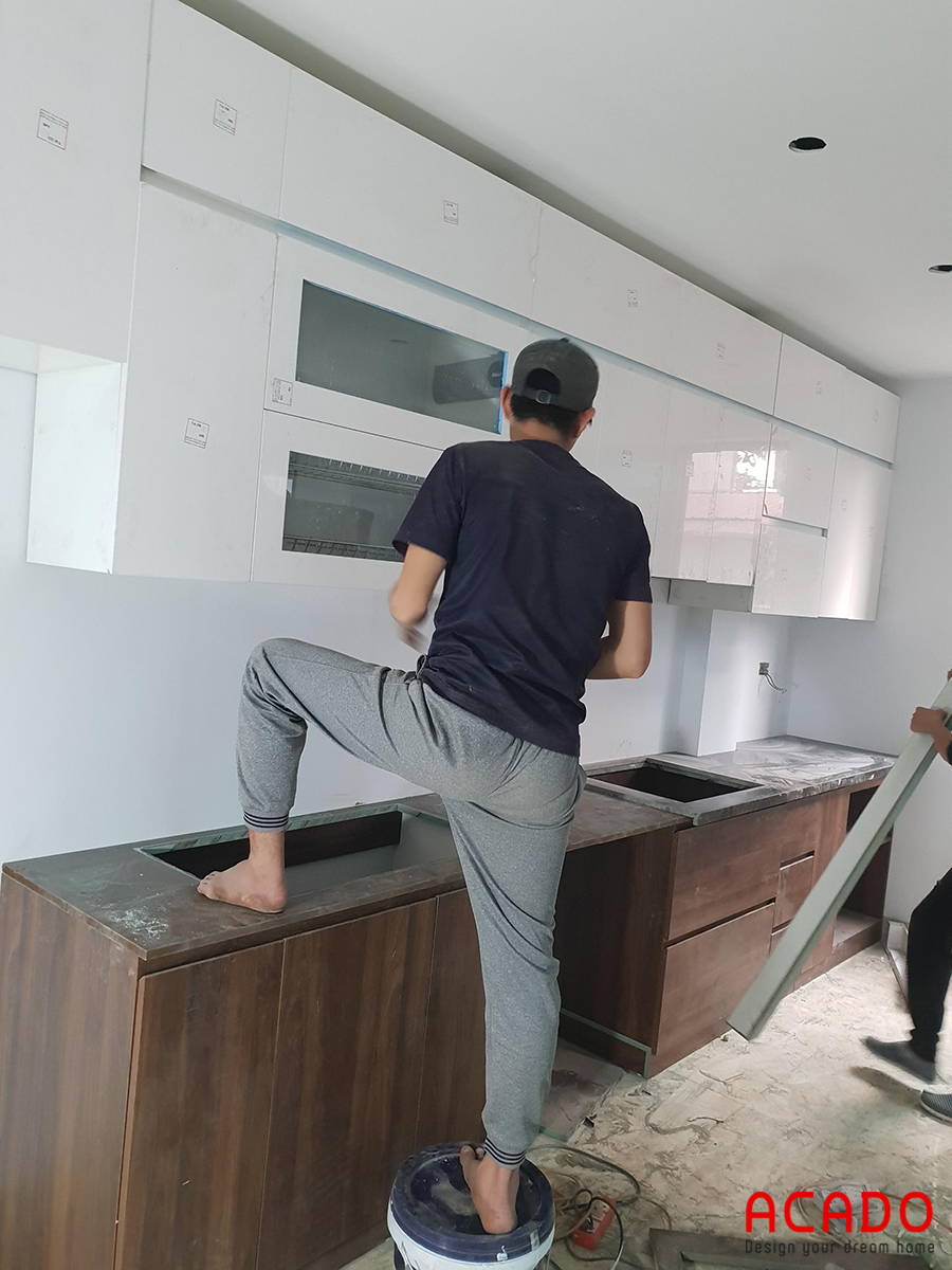 Hình ảnh thợ thi công đang tiến hành lắp đặt tủ bếp.
