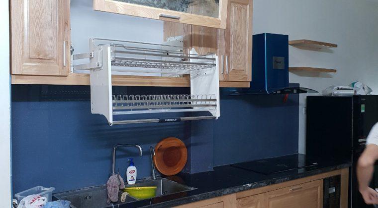 Tủ bếp gỗ tự nhiên kiểu dáng thông minh, sử dụng phụ kiện bếp giá bát nâng hạ giúp người nội trợ dễ dàng hơn trong việc cất bát đũa