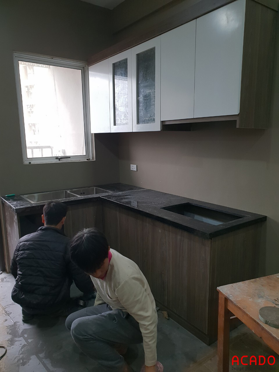 Hình ảnh anh em thợ đang miệt mài lắp đặt tủ bếp.