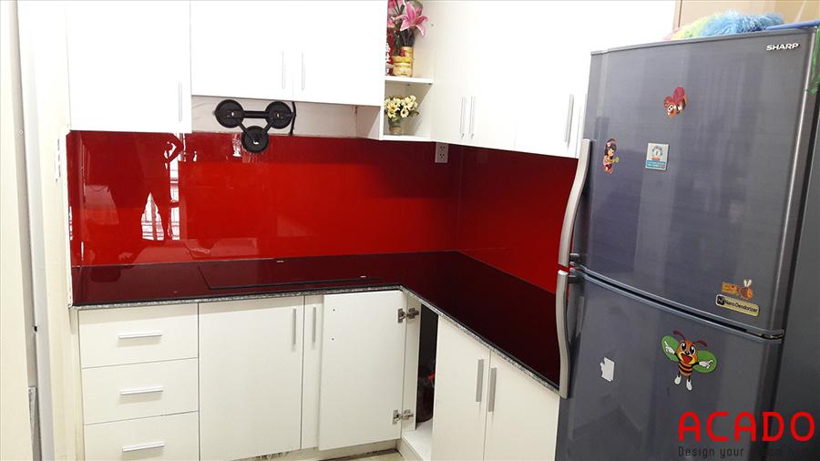 Tủ bếp gỗ công nghiệp Acrylic trắng bóng kết hợp kính bếp màu đỏ làm điểm nhấn,thu hút mọi ánh nhìn.