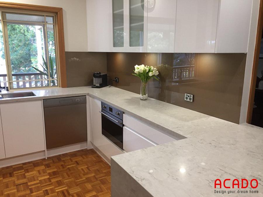 Tủ bếp gỗ công nghiệp trắng , kính bếp màu nâu đất mang đến không gian bếp snag trọng, hiện đại.