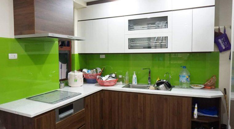 Tủ bếp Melamine trắng kết hợp màu vân gỗ ấm cúng, hiện đại kính bếp màu xanh làm điểm nhấn