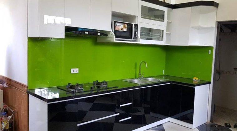 Tủ bếp gỗ công nghiệp sử dụng kính bếp màu xanh lá tạo điểm nhấn cho căn bếp