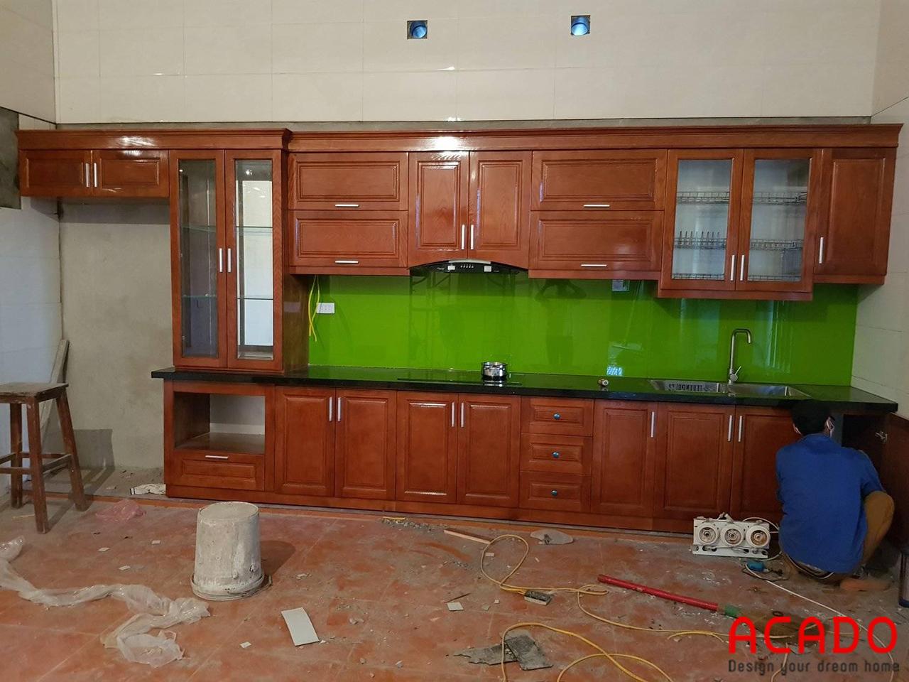 ACADO thi công tủ bếp gỗ xoan đào chữ I và kính bếp màu xanh lá cho gia chủ