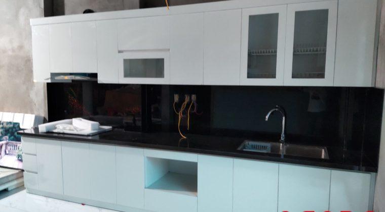 Sự kết hợp giữa tủ bếp Melamine màu trắng và kính bếp màu đen tạo nên một không gian hiện đại