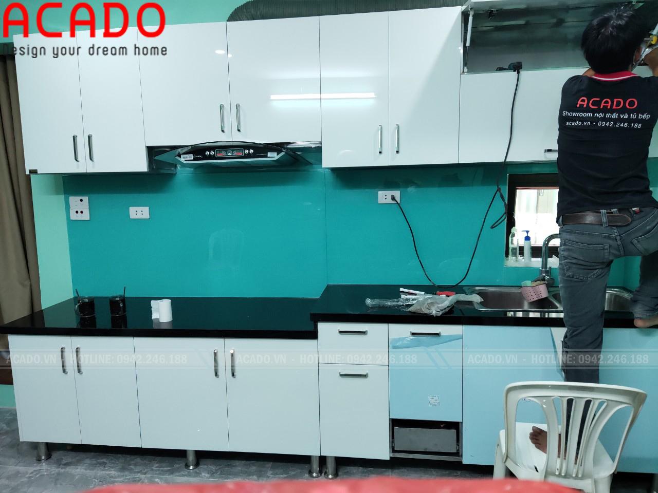 Thợ thi công thực hiện quá trình lắp đặt tủ bếp cho gia đình anh Hải