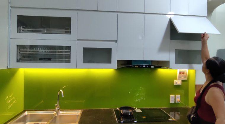 ủ bếp inox cánh acrylic kết hợp với kính ốp bếp xanh tạo không gian tươi mới